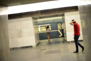 A woman and a man hold their heads as they walk toward a train at a Russian Metro station in Moscow August 11, 2013. To step onto the Moscow metro is to step back in time and immerse yourself in a museum rich in architecture and history. Opened in 1935, it is an extravagant gallery of Communist design, featuring Soviet artworks, statues, chandeliers, stained glass and ceiling mosaics. Built under Stalin, the metro now transports 7 to 9 million people a day and costs 30 Rubles, around $1, for a single ride. Picture taken August 11, 2013. REUTERS/Dylan Martinez (RUSSIA - Tags: TRANSPORT SOCIETY) ATTENTION EDITORS: PICTURE 08 OF 24 FOR PACKAGE 'RIDING THE MOSCOW METRO' SEARCH 'MOSCOW CHANDELIERS' FOR ALL IMAGES - RTX134PR