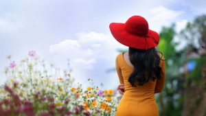 6968126-girl-brunette-yellow-dress-red-hat-flowers