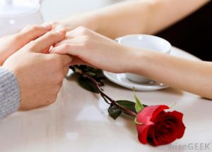 man-and-woman-holding-hands-on-table-with-red-rose
