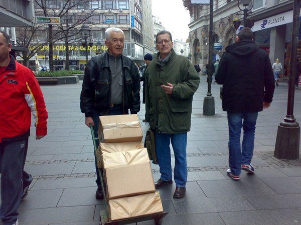 Miladin Ševarlić,desno, prevozi sa kolegom Draganom Tomićem, izdanja Udruženja dramskih pisaca Srbije preko Trga Republike.