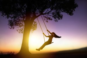 silhouette of happy young woman on a swing with sunset background