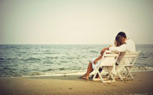 Romantic_Couple_Seating_on_Beach_Wallpaper_Download
